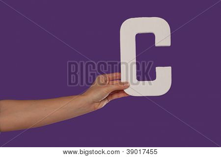 Female hand holding up the uppercase capital letter C isolated against a purple background conceptual of the alphabet, writing, literature and typeface