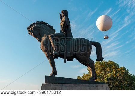 Statue Of King Vakhtang Gorgasali In Tbilisi, Air Excursion Balloon For Passengers Against The Blue