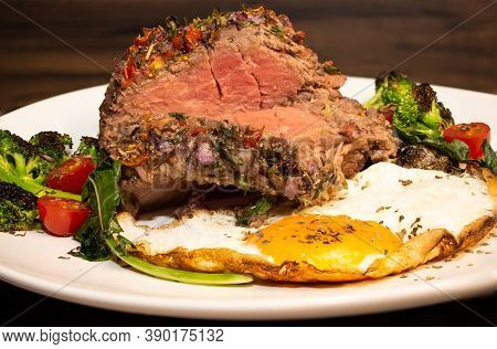 Roasted And Seasoned Meat With Accompaniment Of Fried Egg, Brocolis, Onion And Tomato.