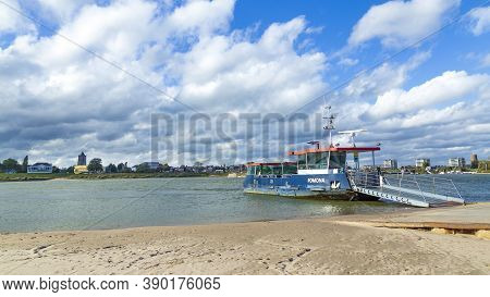 Tiel, Netherlands - October 4, 2020: Skyline Of City Tiel With Ferry Boat Crossing The Waal In Betuw