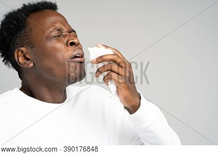 Close Up Of Unhealthy Afro-american Man Blowing Nose And Sneeze Into Tissue Or Napkin, Experiences A