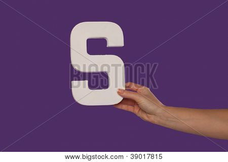 Female hand holding up the uppercase capital letter S isolated against a purple background conceptual of the alphabet, writing, literature and typeface