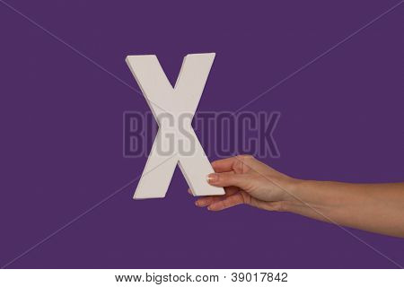 Female hand holding up the uppercase capital letter X isolated against a purple background conceptual of the alphabet, writing, literature and typeface