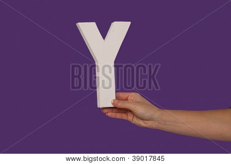 Female hand holding up the uppercase capital letter Y isolated against a purple background conceptual of the alphabet, writing, literature and typeface