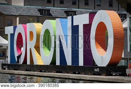 Toronto, Canada - 06 27 2016: A Man Sitting In The Letter Of The Sign Toronto Erected In The Nathan