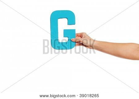Female hand holding up the uppercase capital letter G isolated against a white background conceptual of the alphabet, writing, literature and typeface