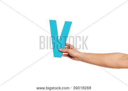 Female hand holding up the uppercase capital letter V isolated against a white background conceptual of the alphabet, writing, literature and typeface