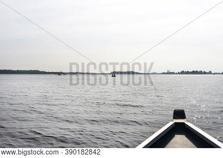 Picture Taken From A Wooden Boat, Visible People Floating On The Boats, The Bow Of The Boat Is Blurr