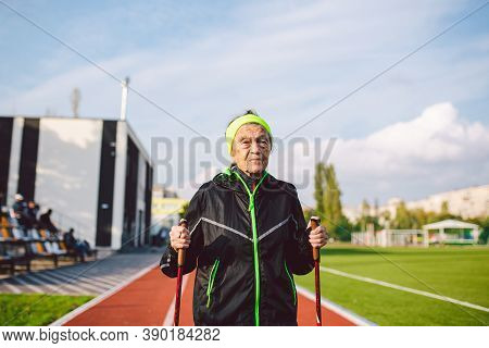 Senior Woman Walking With Walking Poles In Stadium On A Red Rubber Cover. Elderly Woman 88 Years Old
