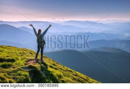 Happy Woman With Backpack And Raised Up Arms On The Peak And Beautiful Mountains In Fog At Sunset. A