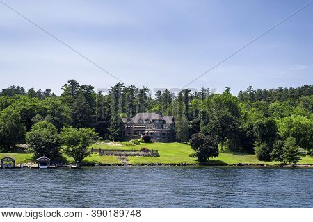 A Large Mansion On The Waterfront Of Lake George In The Summertime In New York.