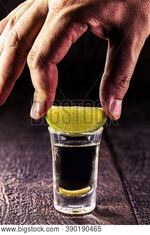 Hand Holding A Glass Of Mezcal (or Mezcal), Typical And Exotic Drink From Mexico, With Larva In The