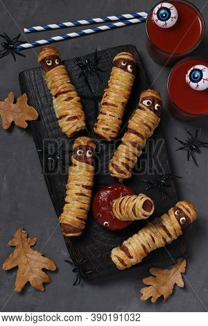 Spooky Sausage Mummies, Tomato Juice And Sauce For Halloween Party On Dark Wooden Board. View From A