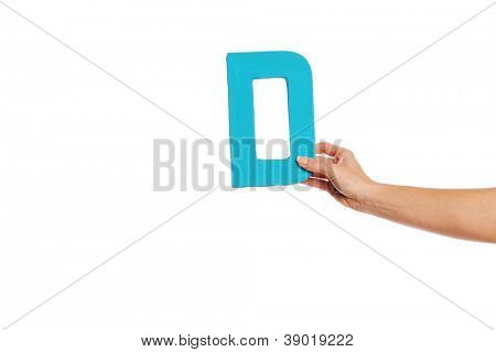 Female hand holding up the uppercase capital letter D isolated against a white background conceptual of the alphabet, writing, literature and typeface