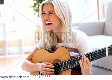 Young Woman Playing Her Guitar At Home