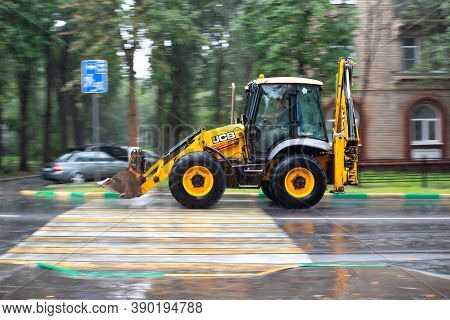 Vidnoe, Russia - August 12, 2020: Yellow Tractor Driving On A Wet Road In The Rain. Wet Downpour, Ag