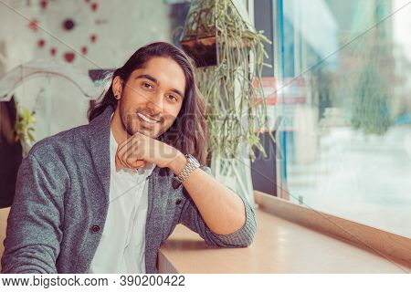 Close-up Of An Adult 30 Years Old Man Smiling Looking At You Camera Sitting At Table Near Window In