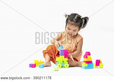 Asian Child Girl In Thai Traditional Dress Sit And Play Colorful Plastic Blocks Or Toy Happily Isola
