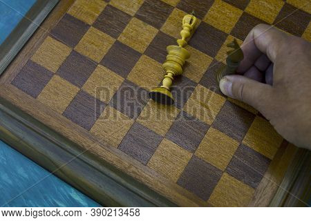 A Hand With A Knight And A Checkmate Position On A Chess Board