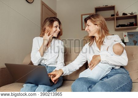 Middle Aged Woman With Her Adult Daughter Sit On The Sofa, Watching Funny Videos Or Photos, Smiling,