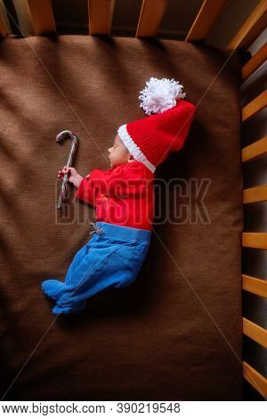Cute Newborn Baby In Santa Hat With Lollipop. Sleeping Baby. Closeup Portrait Of Newborn Baby. Baby