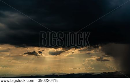 Heaven Sky With God Light Over Mountain Range. Sun Rays Through Dark Clouds. Stormy Sky. Golden Sunl