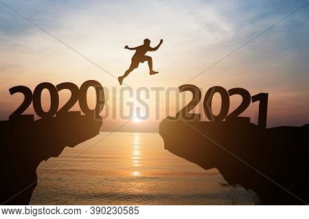 Happy New Year 2021 And Silhouette Concept , Man Jumping From 2020 To 2021 With Beautiful Orange Sky
