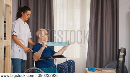 Senior Man With Disability In Wheelchair Doing Recovery Exercise With Therapist. Disabled Handicappe