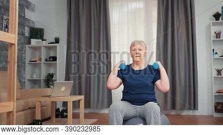 Senior Woman Pumping Shoulder Muscle Using Dumbbells Sitting On Balance Ball. Old Person Training At