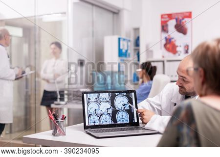 Radiologist Pointing At Brain Ct Scan On Laptop Screen During Senior Woman Check Up In Hospital Offi