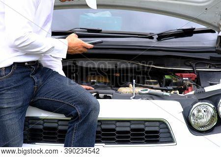 Asian Young Man Sitting On A Broken Car Calling For Assistance And Repaired Wheeled Vehicles On The