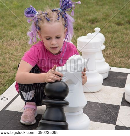 The Girl Hugs Huge Chess Pieces. Two White Horses. The Concept Of Learning A Chess Game. Grandmaster