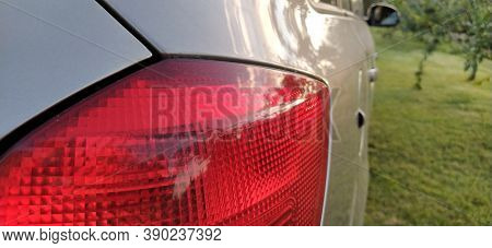 Detail Of The Rear End Of A Silver Car With Focus On The Brake Lights. Red Rear Light Of The Car. Br
