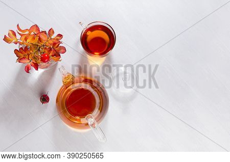 Sunny Autumn Teatime With Rose Hip Tea With Teapot, Cup, Orange Rose Hip Branch With Shadows On Whit