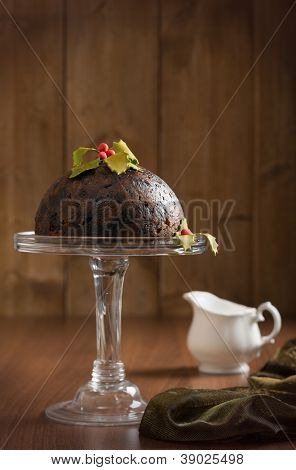 Christmas pudding decorated with holly and berries in rustic setting