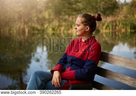 Side View Of Pensive Woman Sitting On Wooden Bench On Bank Of River, Lady With Knot Looking At Water