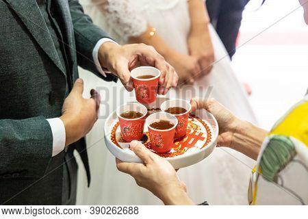 Closeup Of Bridegroom Holding Tea To Serve Elderly During Chinese Wedding Tea Ceremony. Chinese Word