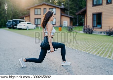 Outdoor Shot Of Fit Healthy Woman Dressed In Active Wear Makes Physical Exercises With Dumbbells In
