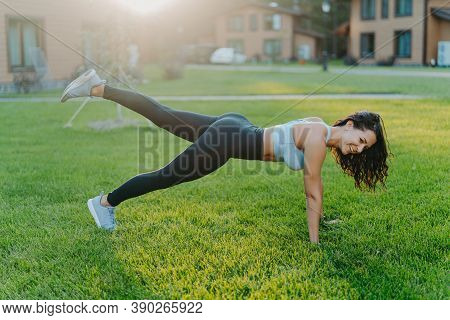 Happy Sporty Woman Stands In Plank Pose, Raises Legs And Does Physical Exercises To Keep Fit, Dresse