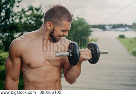 Outdoor Shot Of Strong Muscular Man With Naked Torso Lifts Heavy Barbell And Trains Muscles Has Work