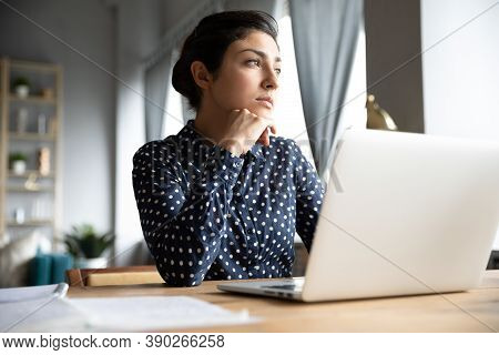 Thoughtful Indian Female Distracted From Computer Work Looking Into Distance