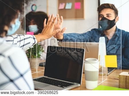 Young People In Co-working Creative Space Wearing Surgical Mask Protection And Keeping Social Distan