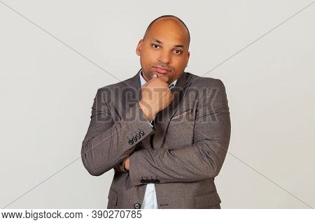 Young Male African American Businessman Holding His Chin With Thoughtful Facial Expression Looking I