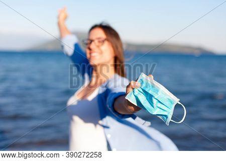 Happy Woman Take Off Medical Mask At Sea Beach. Corona Free Countries. Coronavirus Quarantine Finish