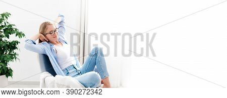 Young Woman Relaxing Under Air Conditioner At Home. Girl Resting On Couch, Enjoying Cool Fresh Air I