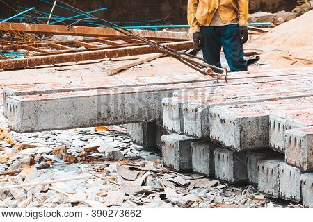 Pile Concrete Pillars On The Ground Worker Move By Sling In Construction Site