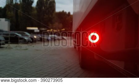 Close-up Shot Of The Rear Round Red Marker Light Of A Truck. Rear Light For A Truck. The Background