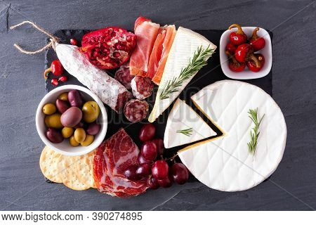 Charcuterie Platter Of Assorted Meats, Cheeses And Appetizers. Above View On A Dark Slate Background