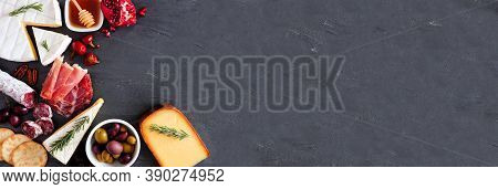 Variety Of Cheese And Meat Appetizers. Top View Corner Border On A Dark Slate Banner Background With
