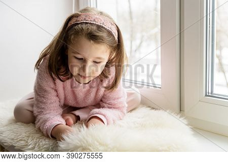 Kid Playing By Window At Home Alone In Winter, Cute Little Girl Sitting On Fur Rug On Sill In Room.